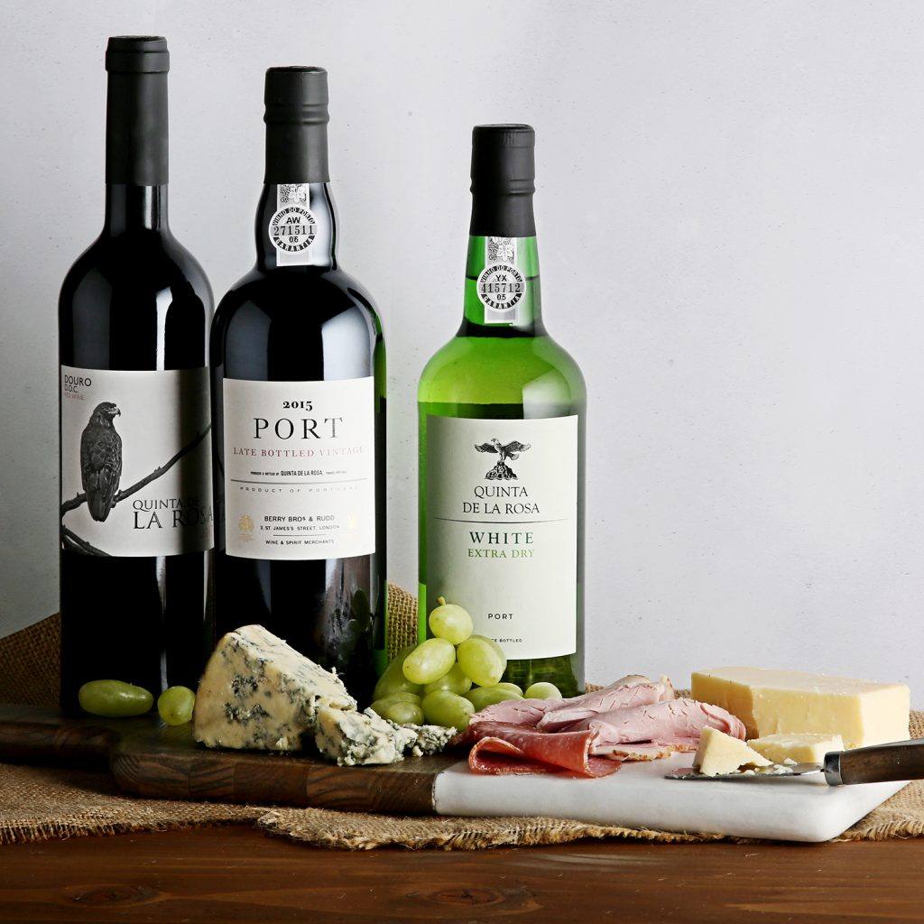 Three bottles of Port alongside a cheese and meat board