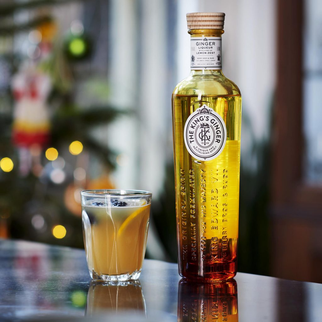 A bottle of the newly redesgined King's Ginger stands next to a small mulled cocktail