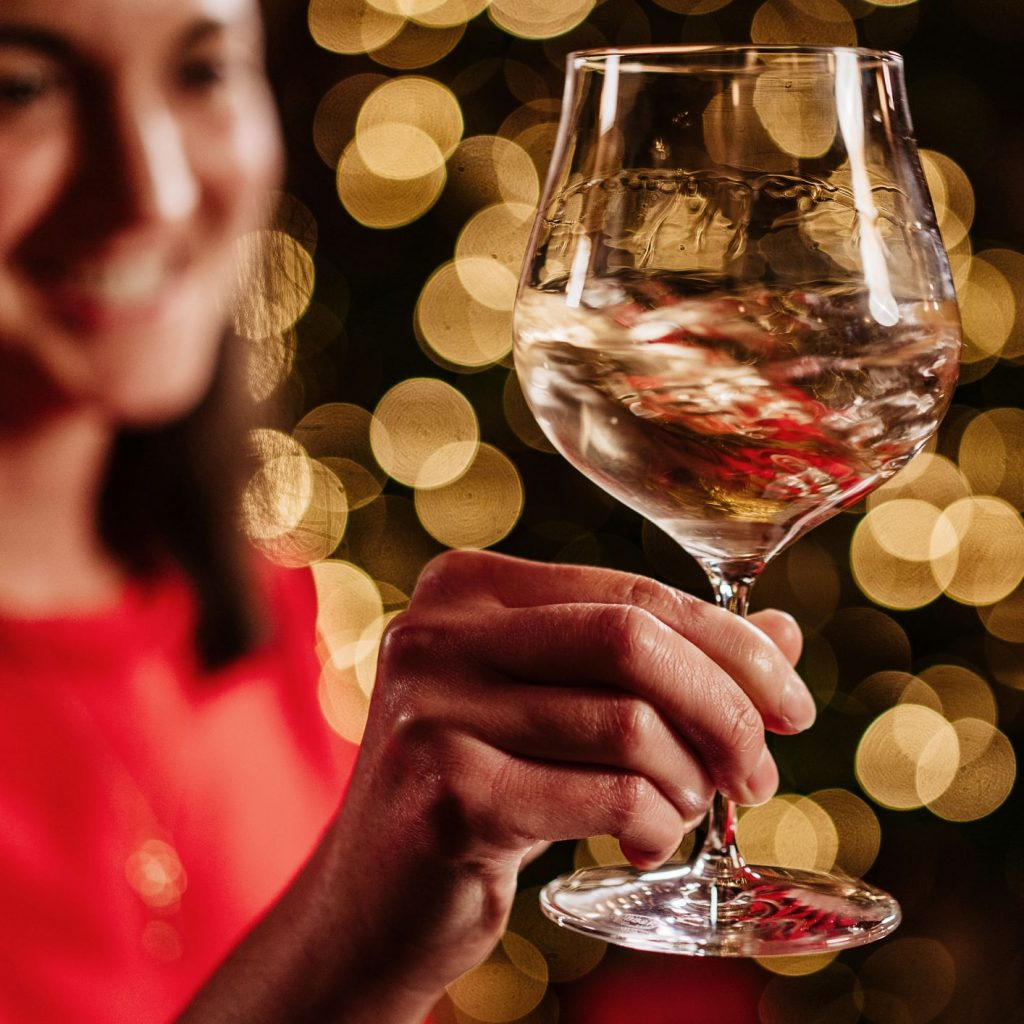 Isabella Cameron, fine wine specialist, holds a glass of white wine at Christmas