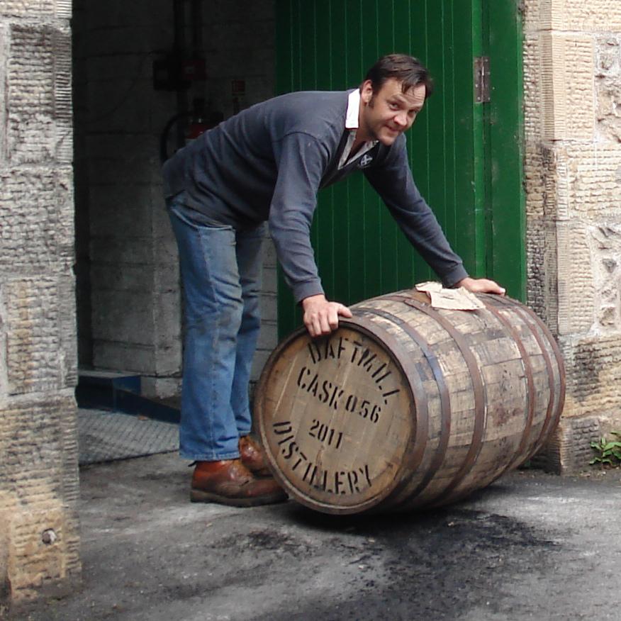 Francis Cuthbert, farmer and distiller, rolls a cask out of the Daftmill distillery door