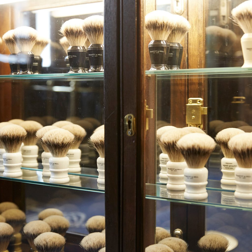 A glass cabinet filled with shaving brushes at grooming venue Truefitt & Hill