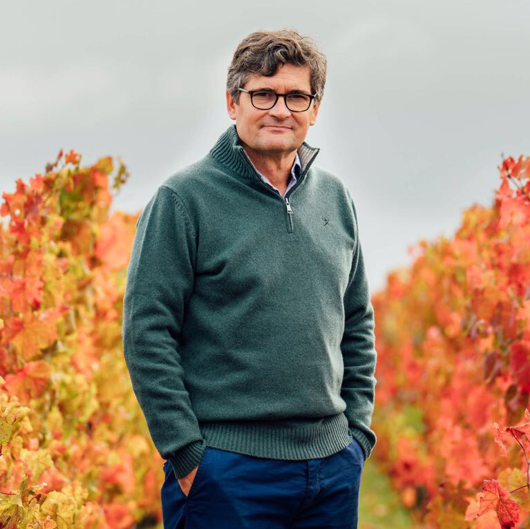 Henri Lurton stands in his vineyard at Ch. Brane-Cantenac, against a backdrop of golden autumnal vines.