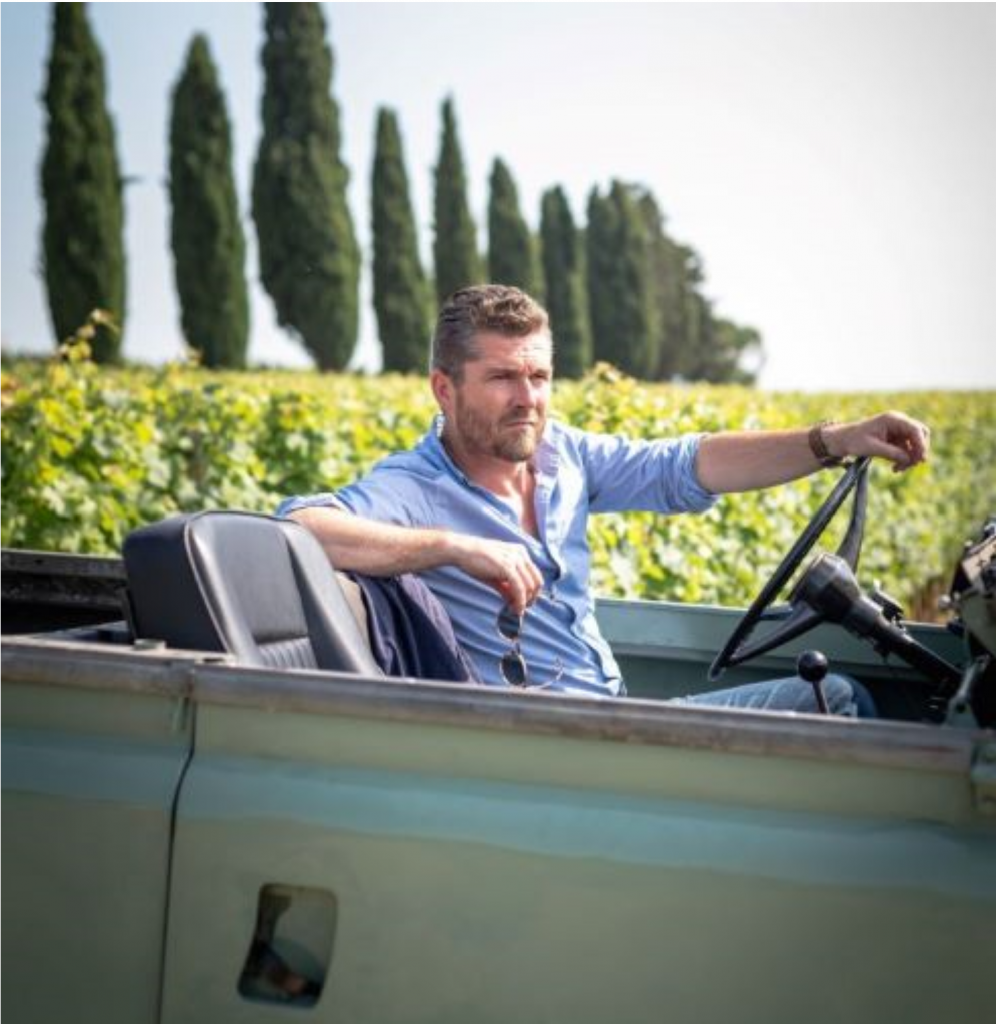winemaker Nicolas Audebert drives an open-top 4-wheel drive along the edge of Berliquet's vineyards. Cyprus trees stand in the background