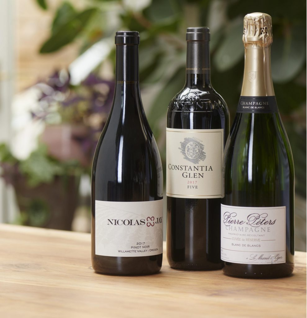 The three favourite bottles, as selected by our experts, are standing on top of a wooden table against a background of green leaves.