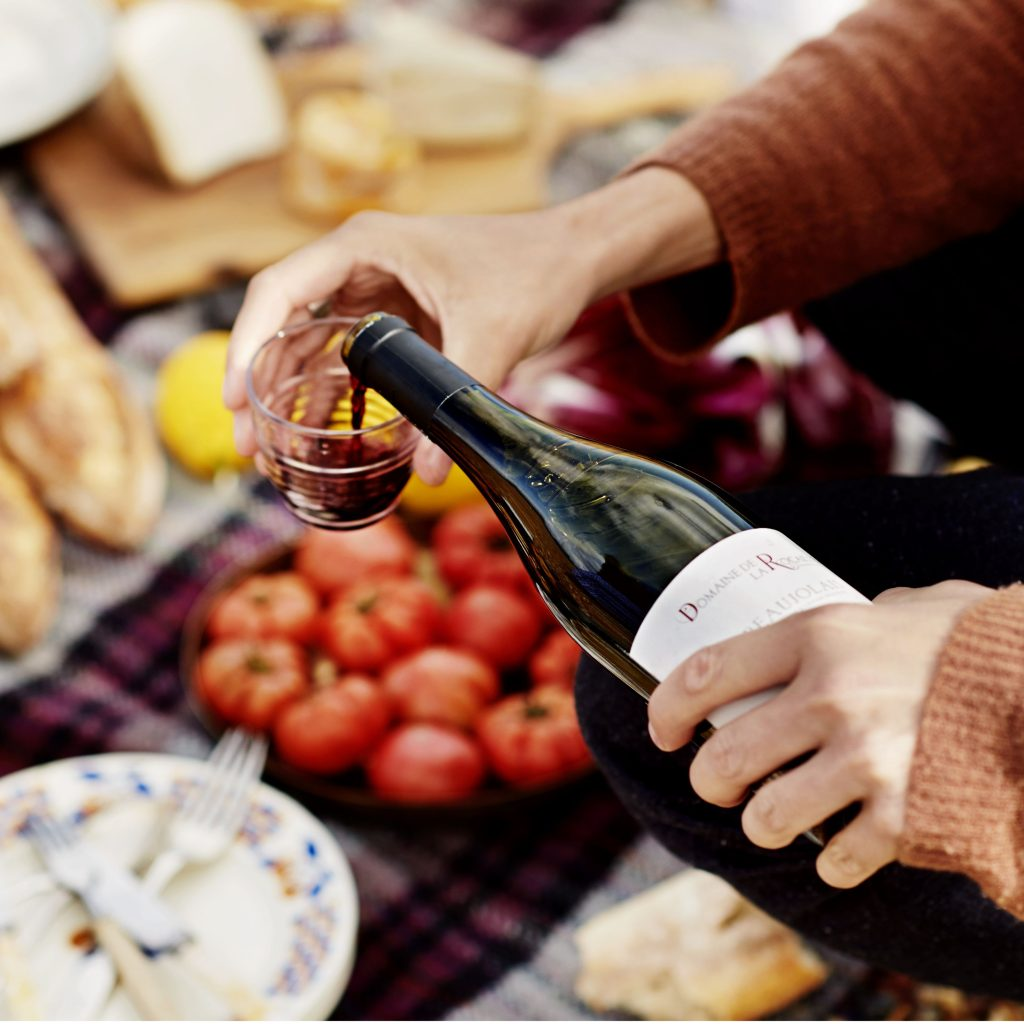 A photo showing someone pouring a glass of Beaujolais against a backdrop of picnic dishes laid out on the ground.