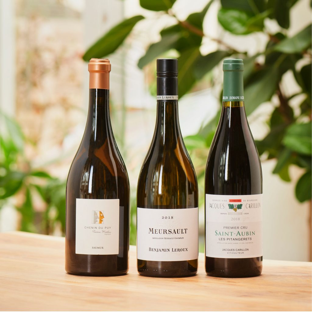 A photograph of three bottles of wine chosen by our experts, sitting on a wooden table against a backdrop of green house plants