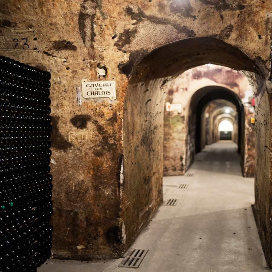 An image of arches and pathways through an underground cellar, where the Champagnes are aged.