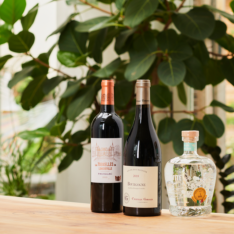 A photo of two wines and a spirit sitting atop a beech table, against a backdrop of green houseplants.