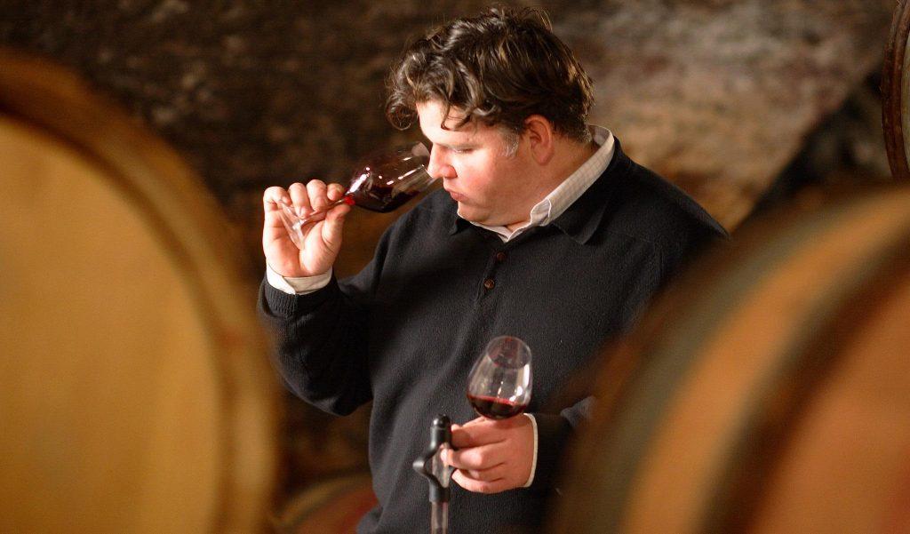 Winemaker Thibault Liger-Belair among the barrels nosing a glass of red Burgundy.