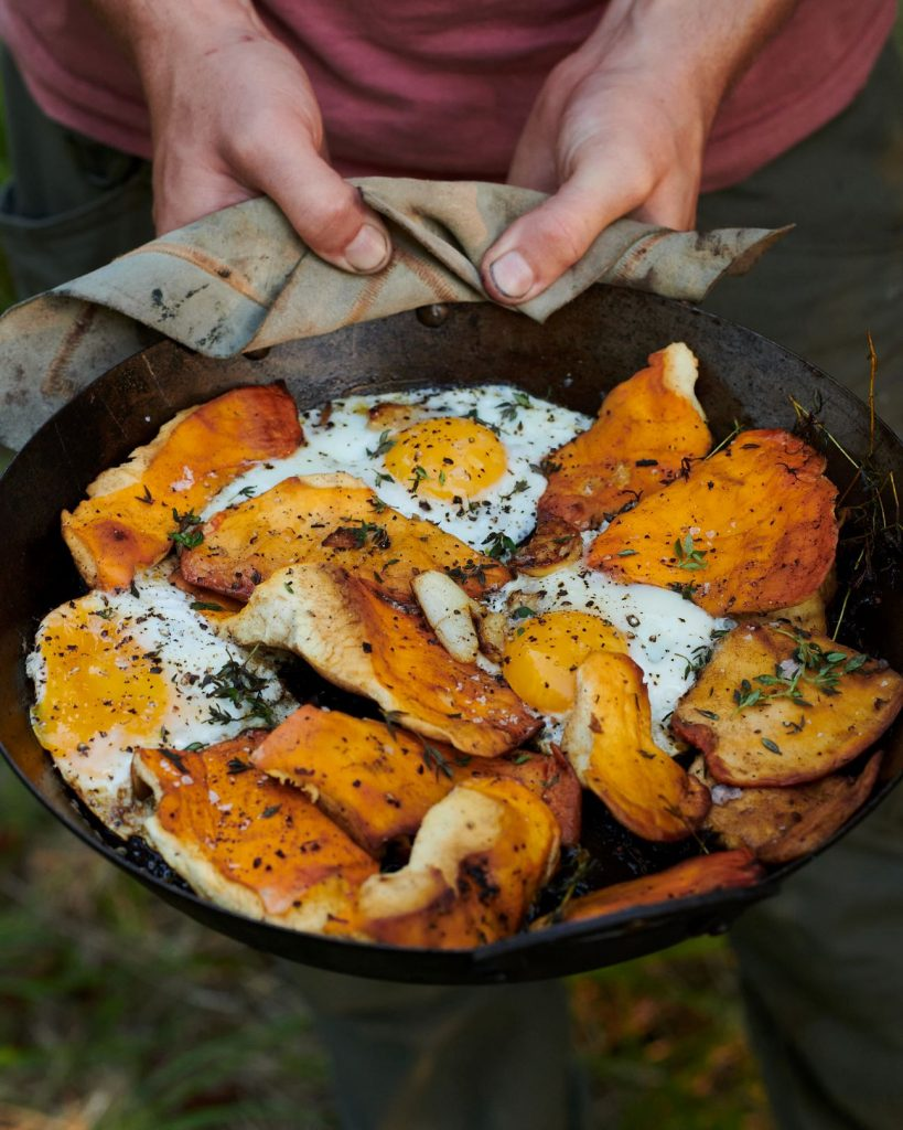 A rustic pan filled wtih foraged mushrooms, cooked with garlic and butter with runny eggs