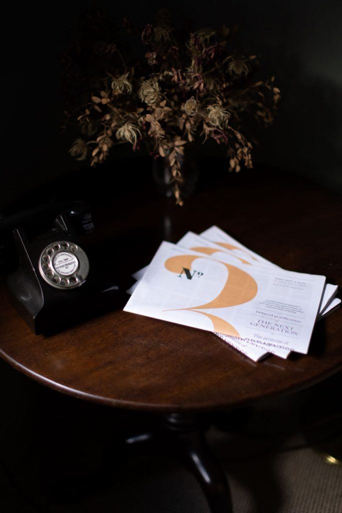 Copies of No.3 magazine are arranged on a table at No.3 St James's Street. An old-fashioned phone and dried flowers decorate the table.