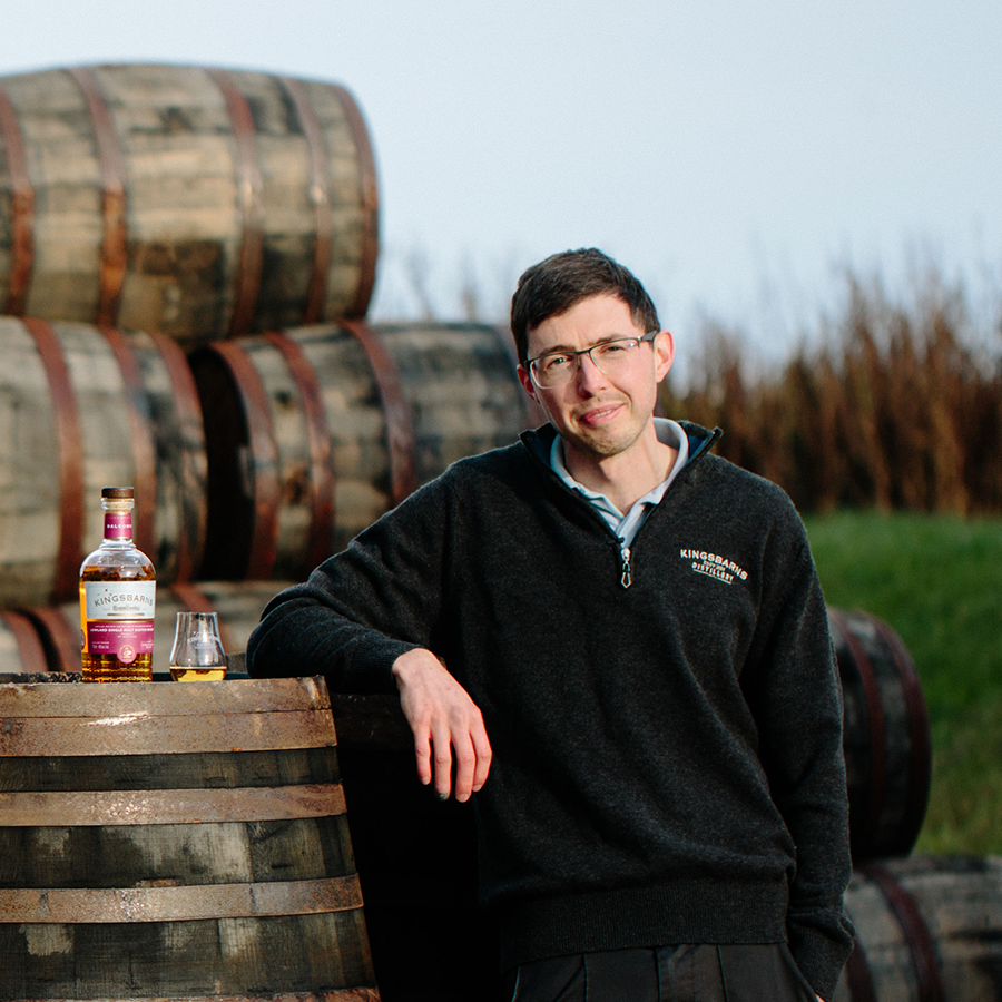 Peter Holroyd, Distillery Manager at Kingsbarns, stands against a backdrop of wooden barrels, beside a bottle of Kingsbarns whisky and a glass.